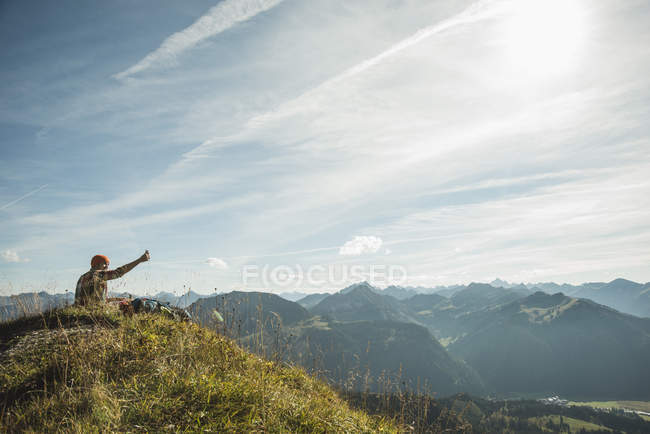 Austria, Tyrol, Tannheimer Tal, young man taking selfie in mountainscape — Stock Photo