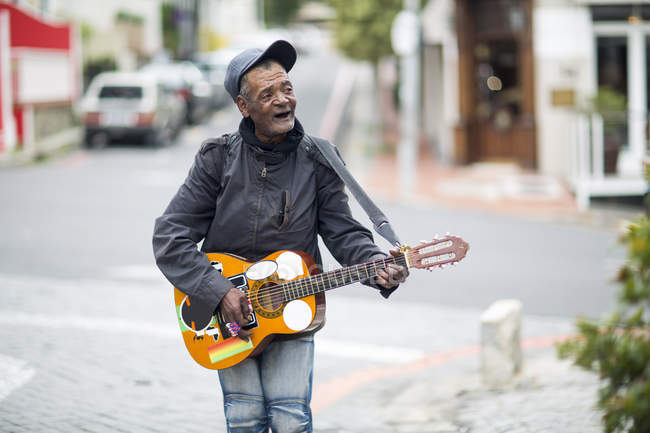 Street musician singing and playing guitar — Stock Photo