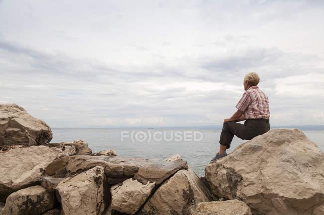 Slovenia, Piran, woman sitting on rocks at waterside looking at horizon — Stock Photo