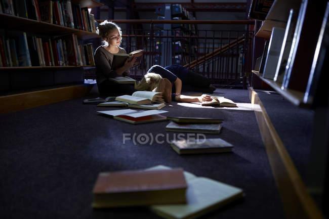 Студентка лежит на полу в библиотеке с подругой, готовящей книгу — стоковое фото
