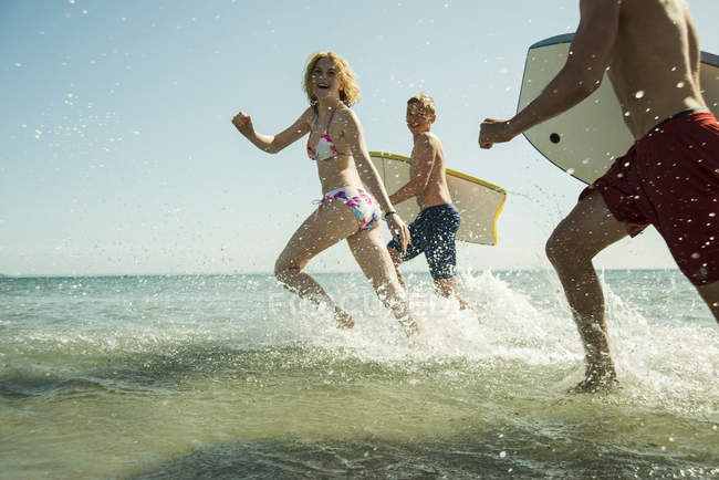 Three teenagers with surfboards running at waterside of the sea — Stock Photo