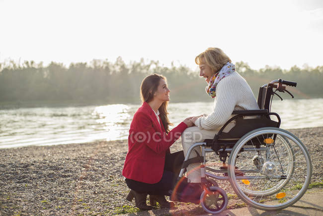 Granddaughter assisting grandmother sitting in wheelchair — Stock Photo