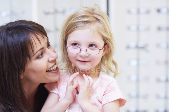 Mädchen passt Brille mit Mutter im Optikergeschäft an — Stockfoto