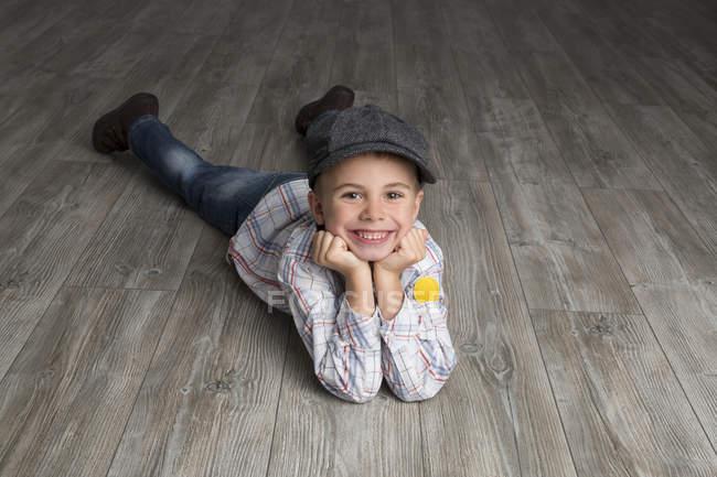 Niño sonriente con gorra tumbado en el suelo en casa - foto de stock