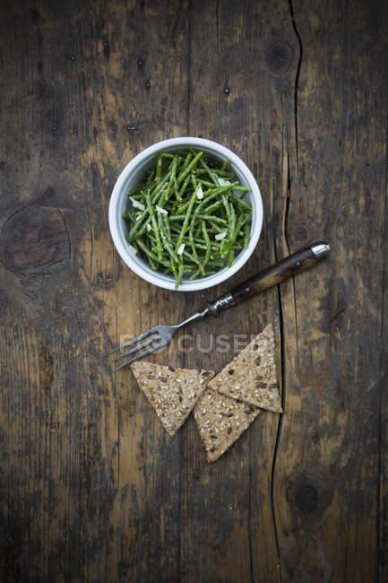 Schüssel Salatsalat und Roggen-Cracker auf dunklem Holz — Stockfoto
