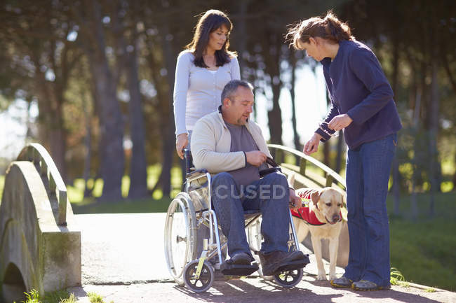 Uomo in sedia a rotelle con donne e cane nel parco — Foto stock