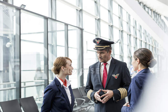 Piloto y asistentes de vuelo en el aeropuerto - foto de stock