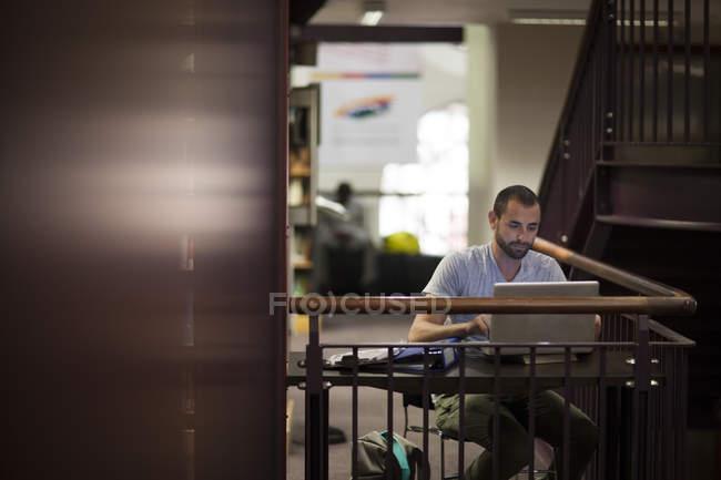 Étudiant utilisant un ordinateur portable dans une bibliothèque — Photo de stock