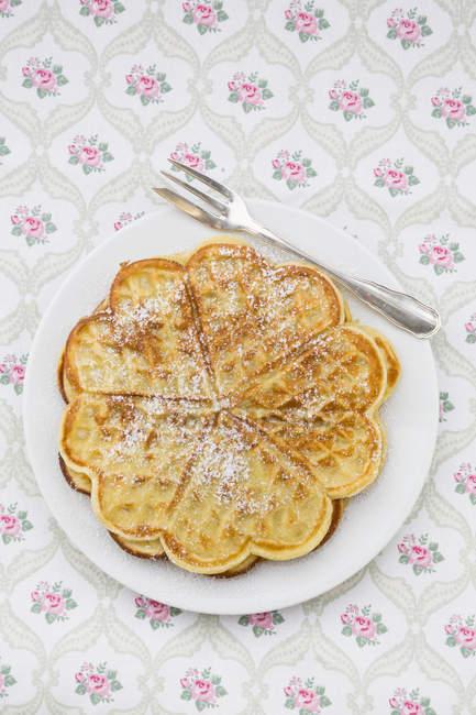 Piatto di cialde cosparso di zucchero sul panno modellato a velo — Foto stock
