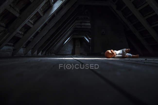 Puppe liegt am dunklen Dachboden — Stockfoto