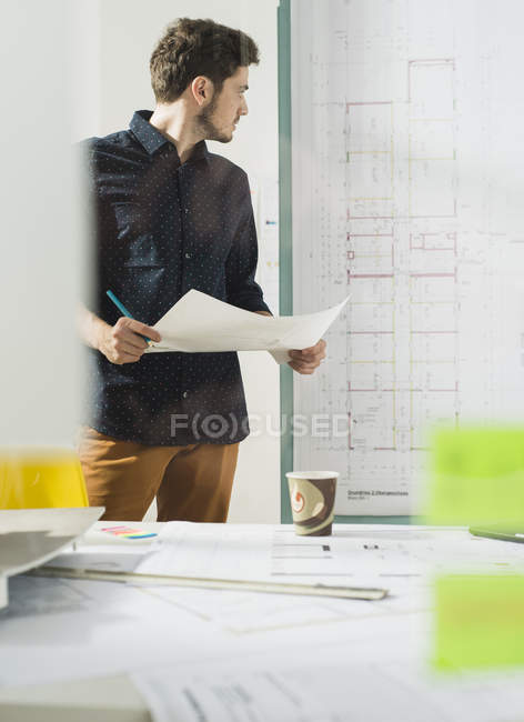 Young architect in office looking at construction plan — Stock Photo
