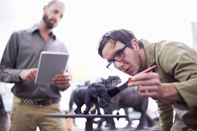 Two men with digital tablet in a sculptor's workshop — Stock Photo