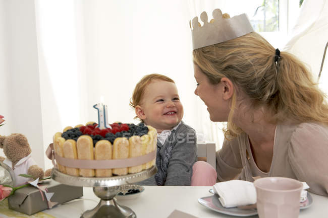 Mother in crown and daughter celebrating little girl first birthday with fancy cake — Stock Photo