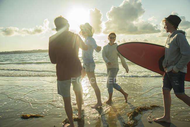 Mulher e três adolescentes caminhando à beira-mar — Fotografia de Stock