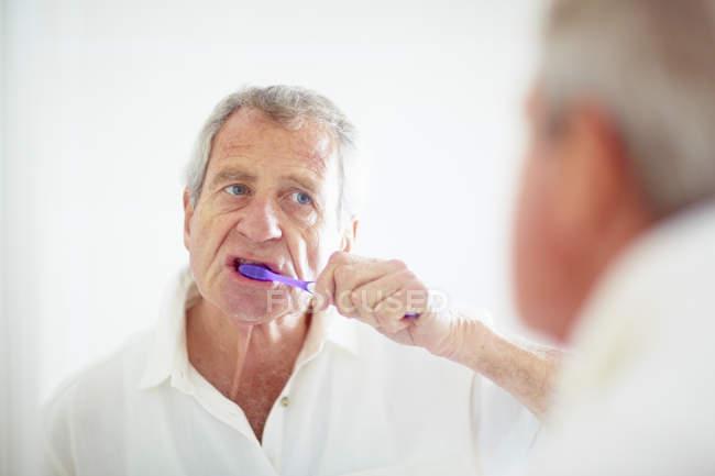 Uomo anziano lavarsi i denti in bagno — Foto stock