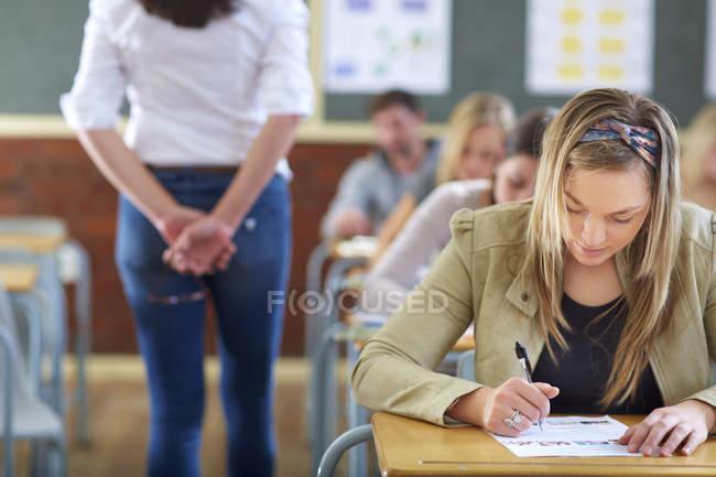 Обрезанный портрет учащихся и учителя в классе во время экзамена — стоковое фото