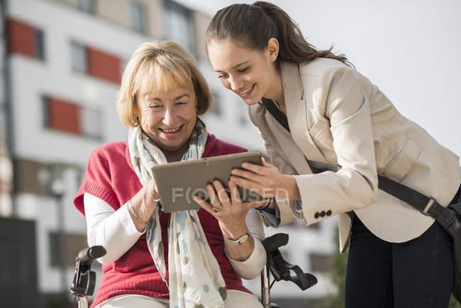 Petite-fille et sa grand-mère regardant tablette numérique — Photo de stock
