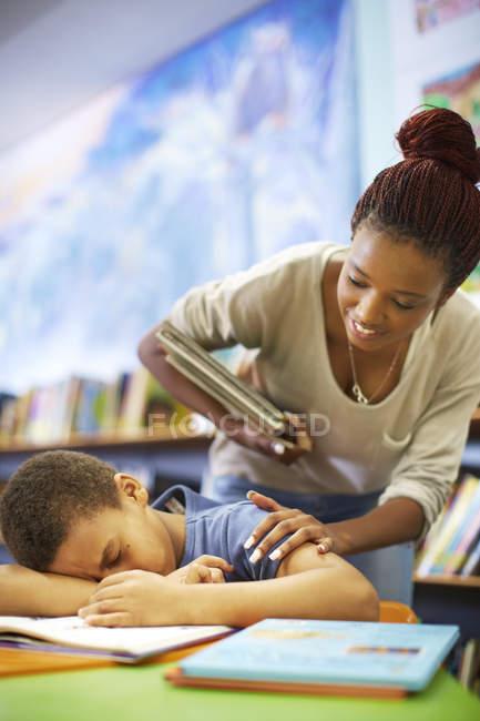 Молодая женщина просыпается спящим мальчиком в библиотеке — стоковое фото