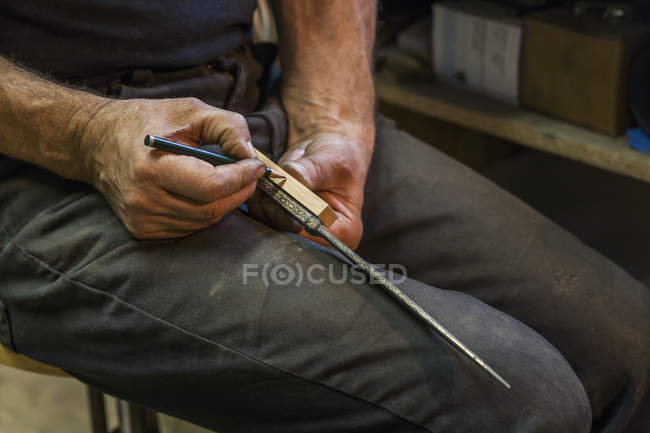 Knife maker drawing marking on knife handle — Stock Photo