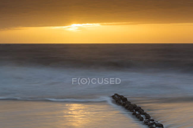 Germany, Schleswig-Holstein, Sylt, North Sea, breakwaters at sunset — Stock Photo