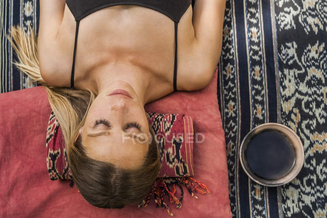 Mulher deitada no cobertor meditando — Fotografia de Stock