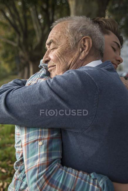 Внук и старший мужчина обнимаются в парке — стоковое фото