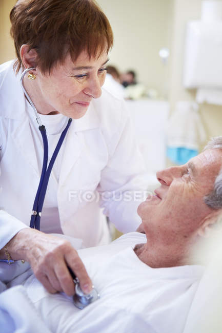 Doctor examining senior man in hospital bed — Stock Photo
