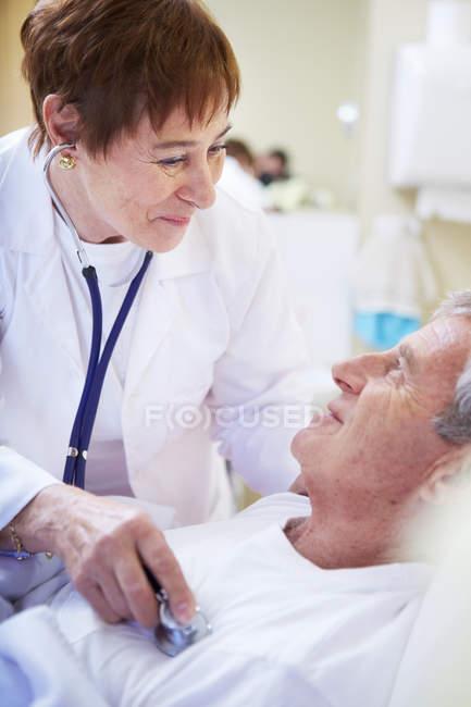 Doctor examinando a mayor hombre en la cama de hospital - foto de stock