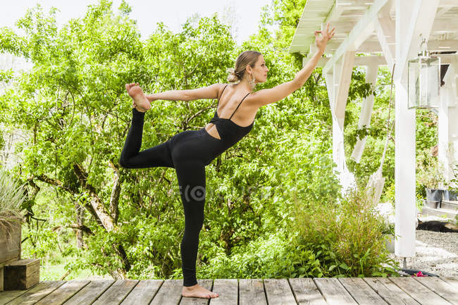 Woman practicing yoga on wooden terrace — Stock Photo