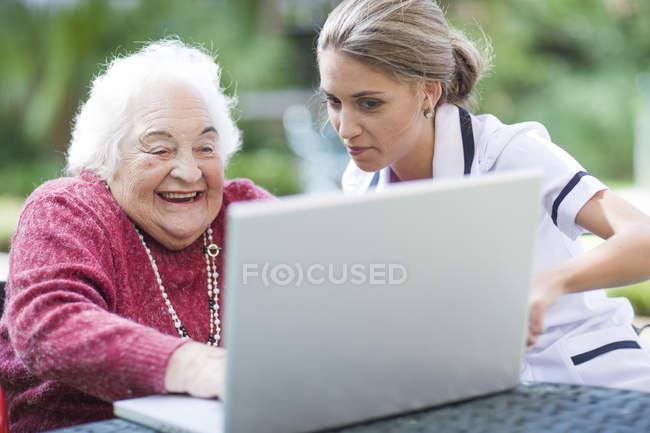 Krankenschwester und Seniorin benutzen gemeinsam Laptop — Stockfoto