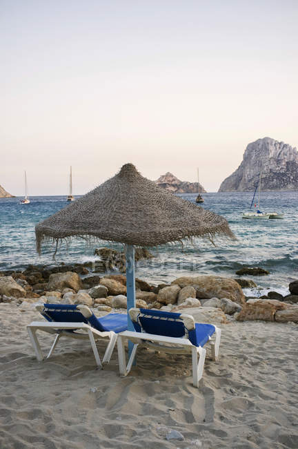 Spain, Balearic Islands, Ibiza, Cala Es Vedra, sunbeds with sunshade in the evening light — Stock Photo