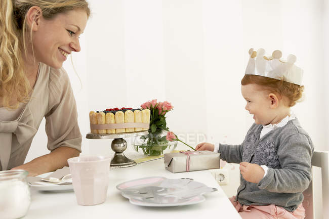 Mother and daughter in crown celebrating little girl first birthday — Stock Photo