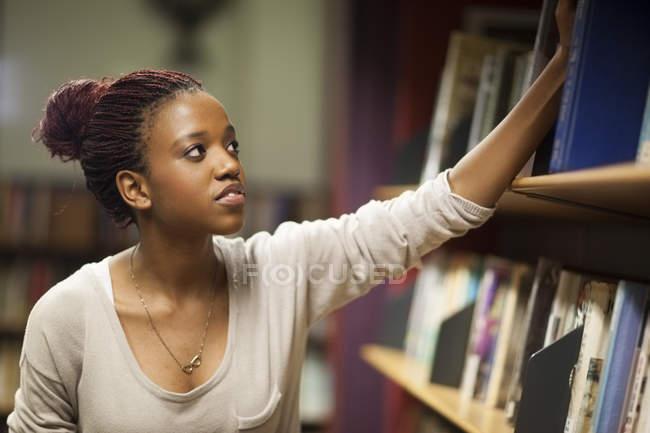 Студентка в библиотеке на книжной полке — стоковое фото