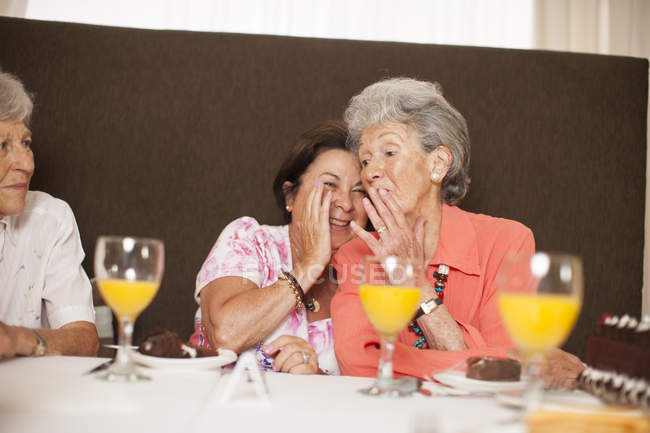 Senior women whispering in a retirement village — Stock Photo
