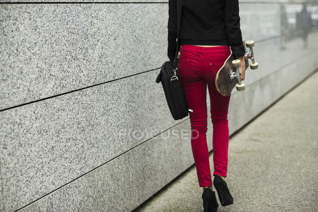 Woman with bag and skateboard — Stock Photo