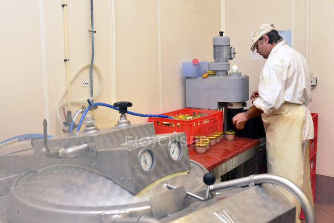 Человек работает консервная машина в мясной лавке — стоковое фото