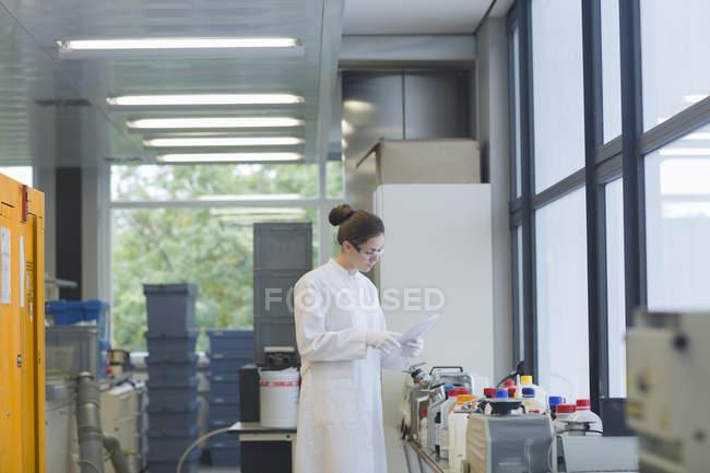 Cientista fêmea permanente com lista em um laboratório de química — Fotografia de Stock