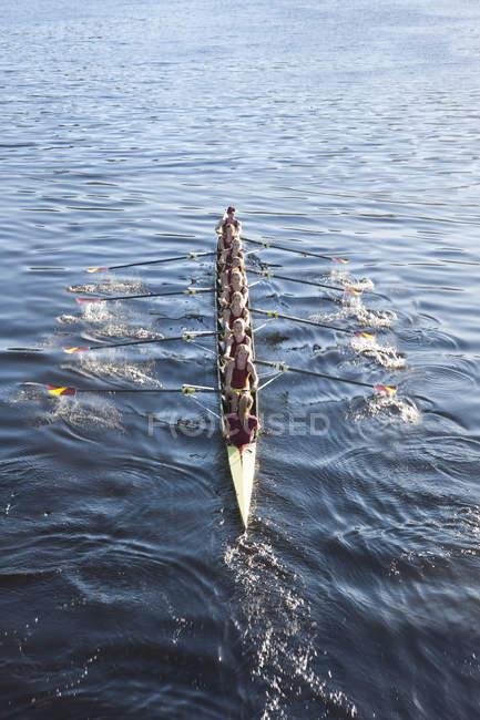 Повышенный вид команды гребцов на лодке в воде — стоковое фото