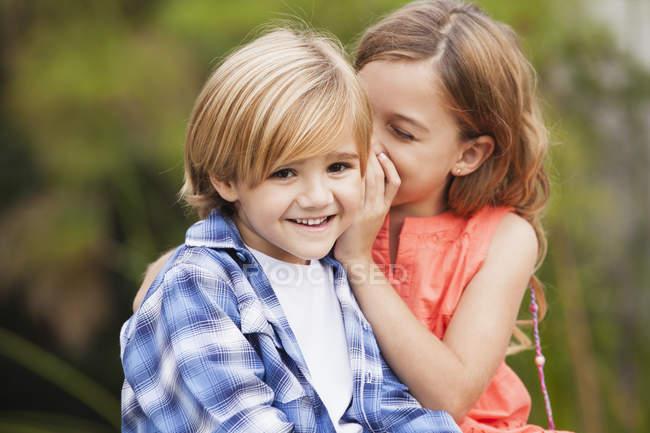 Girl whispering into boy's ear — Stock Photo