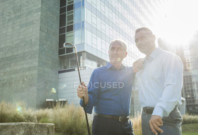 Два бизнесмена с клюшками для гольфа стоят возле офисного здания — стоковое фото