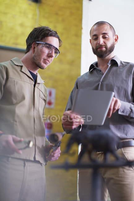 Zwei Männer mit digital-Tablette in einem Bildhaueratelier — Stockfoto