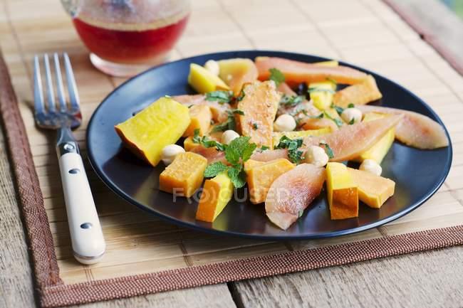 Тыква, сладкий картофель Айва салат с фундуком и свежей нарезанной зеленью служил на черном пластины — стоковое фото