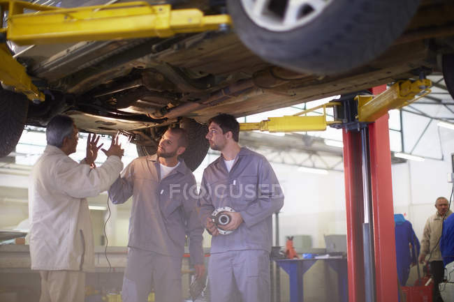 Car mechanics with client in repair garage — Stock Photo
