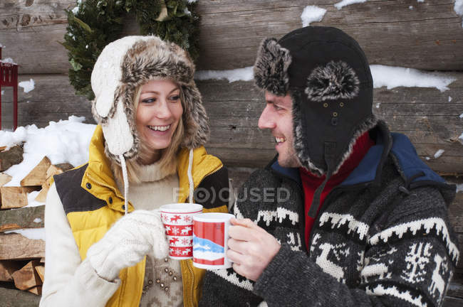 Couple clinking cups at wooden hut in winter — Stock Photo