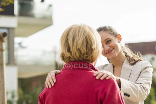 Smiling young woman with hands on shoulders of her grandmother — Stock Photo