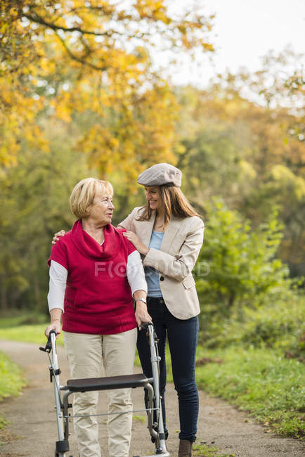 Senior woman and her adult granddaughter walking together in autumnal park — Stock Photo
