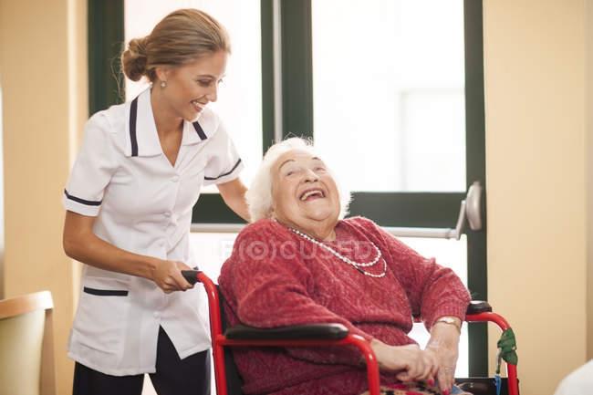 Krankenschwester, die Fürsorge für ältere Frau im Rollstuhl — Stockfoto