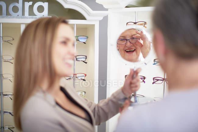 Консультант по оптике пожилая женщина в магазине — стоковое фото