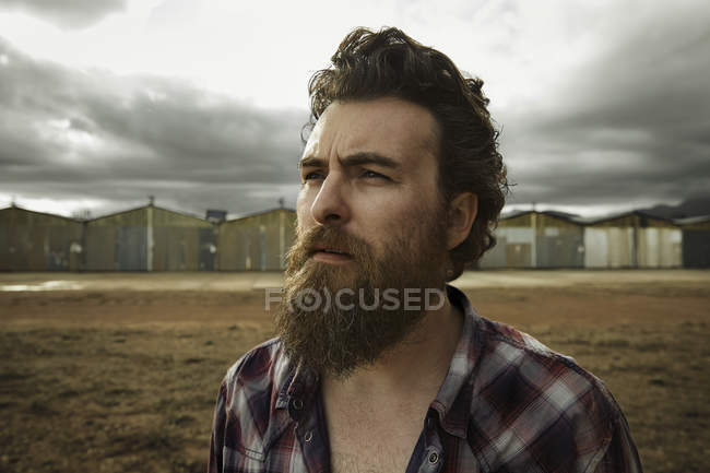 Serious man with full beard in abandoned landscape — Stock Photo