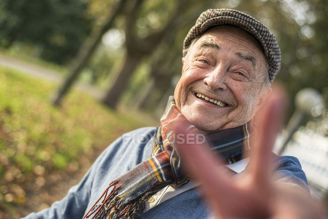 Portrait of happy senior man outdoors doing victory sign — Stock Photo